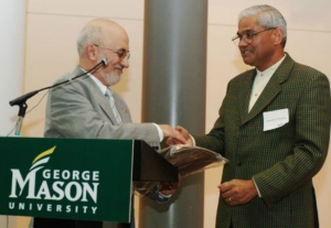 Jagadish Shukla, right, receives an award from colleague Menas Kafatos in 2005.  (Photo: Lisa McCarty/George Mason University)