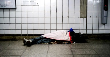 A homeless individual sleeps in a subway station in New York on Wednesday, December 16, 2015. (© Richard B. Levine)