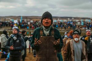 During a Nov. 23 protest targeting the Dakota Access pipeline, Frankie Tso Jr. prays among other demonstrators at the foot of a hill off the Missouri River surrounding the Standing Rock Indian Reservation. (Photo: Natasha Dangond/Polaris/Newscom)