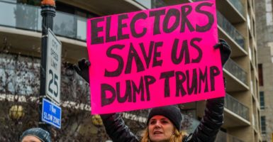 In an anti-Donald Trump protest on Dec. 12 in New York, one woman displays a sign calling for presidential electors to reject Trump, before the Electoral College votes on Dec. 19. (Photo: Erik McGregor/Pacific Press /Newscom)